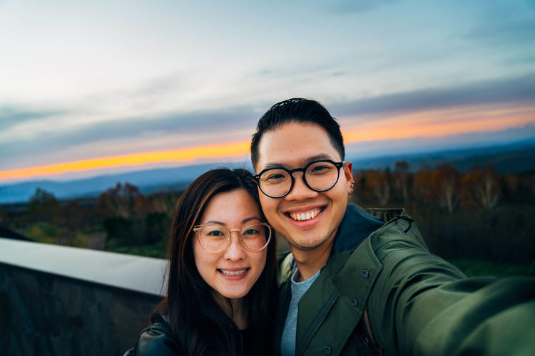 Portrait of smiling couple taking selfie against sky during sunset