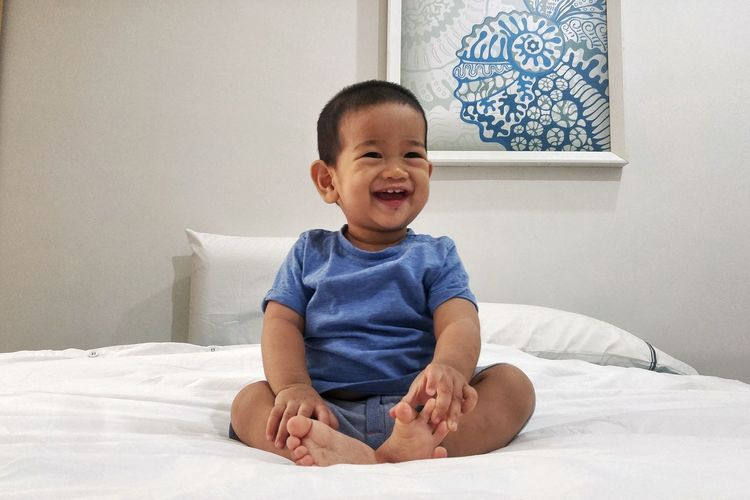 Smiling sitting baby Sitting Portrait Smiling Childhood Bedroom Sitting Full Length Cheerful Happiness Child Cute Babyhood Toddler  Thoughtful Baby Clothing Pillow Posing 0-11 Months Baby Baby Boys Babies Only