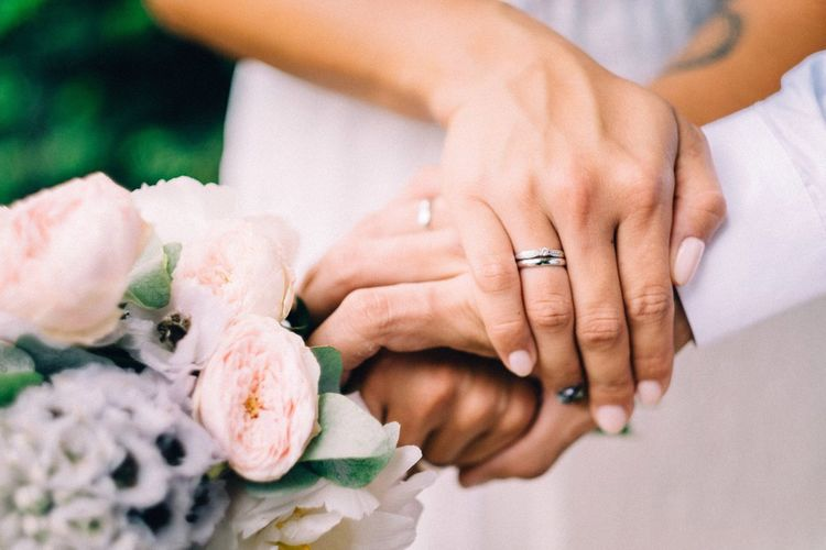 Cropped image of wedding couple holding hands