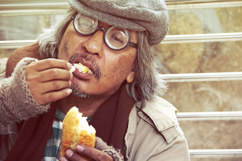 Homeless man on street and eating old bread. Adult Beard Clothing Eating Eyeglasses  Food Food And Drink Front View Glasses Hat Holding Hungry Leisure Activity Lifestyles Mid Adult One Person Outdoors Portrait Real People Snack Unhealthy Eating Warm Clothing