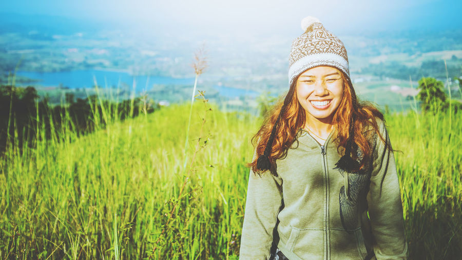 Portrait of smiling young woman standing in farm