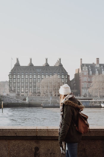 Young woman looking at buildings by canal