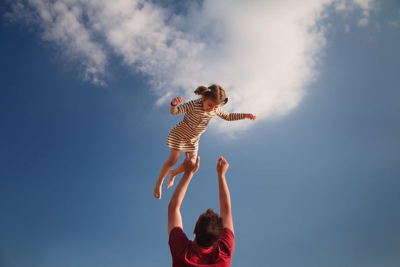 Low angle view of father tossing daughter mid air against sky