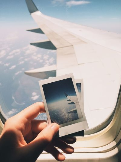 Cropped hand holding picture frame against airplane window