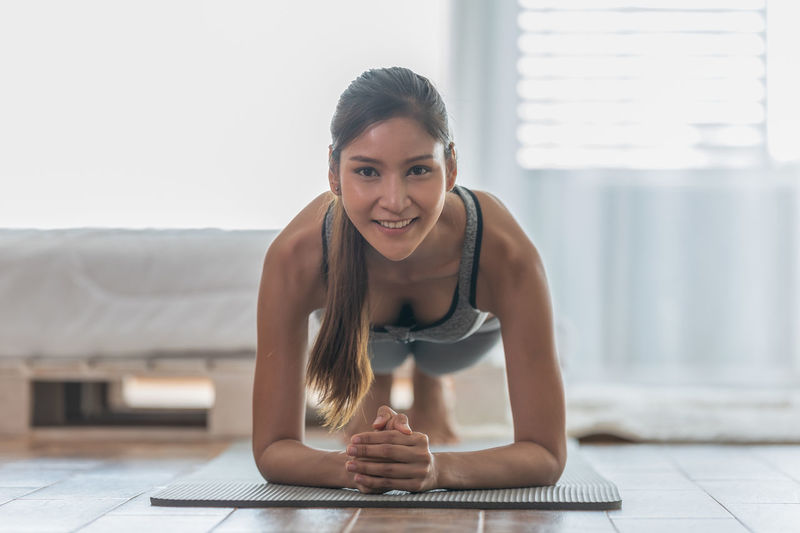 Portrait of smiling young woman exercising at home