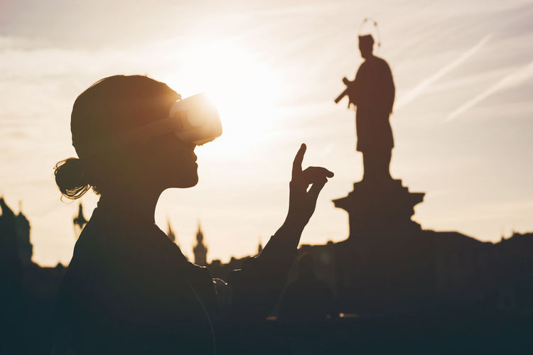 Silhouette woman standing against statue during sunset