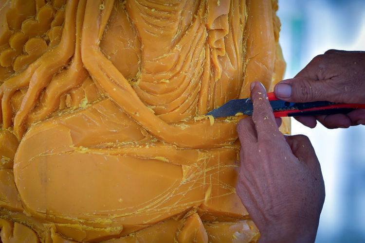 Cropped hands carving wax