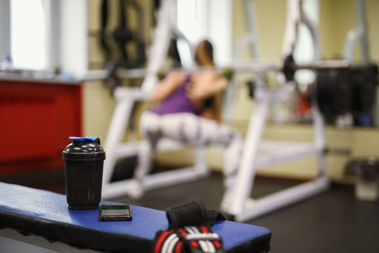 Woman exercising with water bottle in foreground