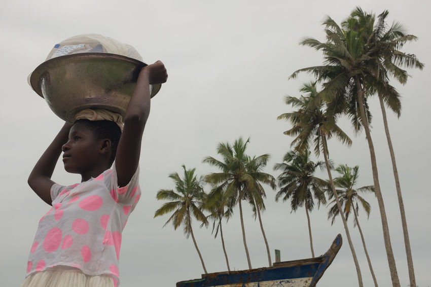 The water seller, Elmina. Elmina Elmina Castle Ghana Travel Child Childhood Holding One Person Palm Tree Real People Sky Tree Tropical Climate Water Water Seller Women