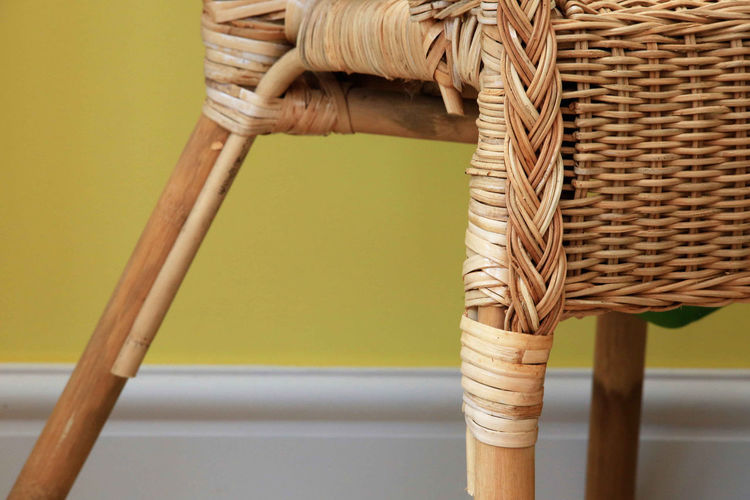 Cropped Image Of Wicker Chair Against Yellow Wall