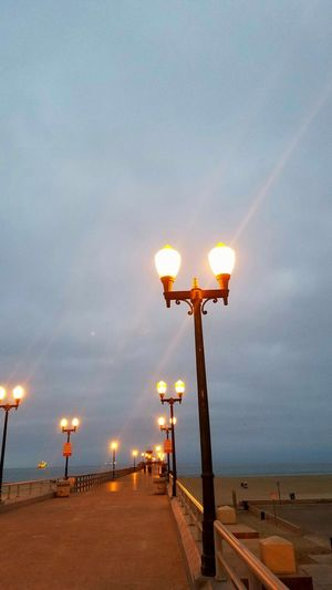Illuminated street light by sea against sky at sunset