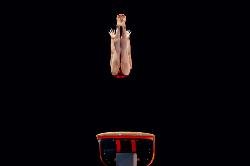 Low angle view of female gymnast jumping against black background