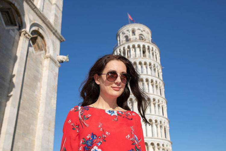 Smiling woman standing against leaning tower of pisa in italy