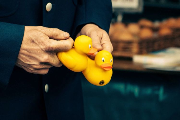 Midsection of man holding yellow rubber ducks