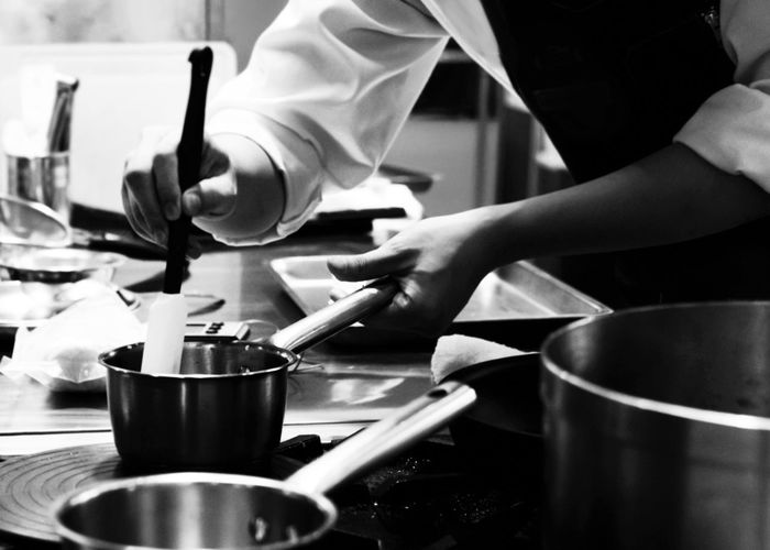Midsection of man preparing food in restaurant