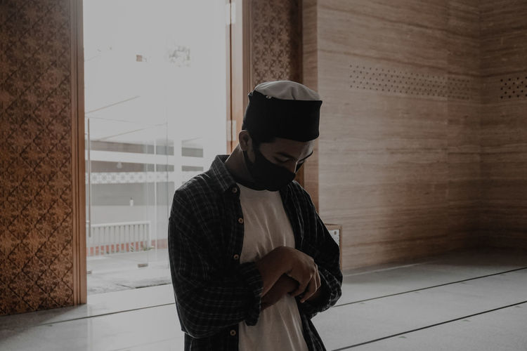 Asian muslim man praying shalat with mask during the covid-19 or corona virus pandemic at the mosque