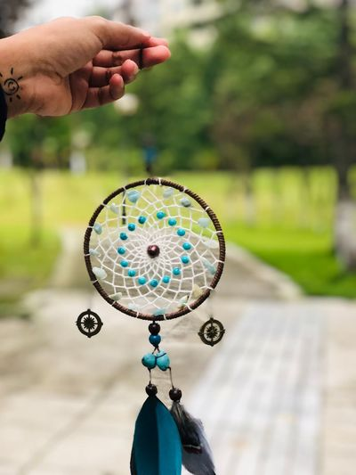Close-Up Of Hand Holding Dreamcatcher Outdoors