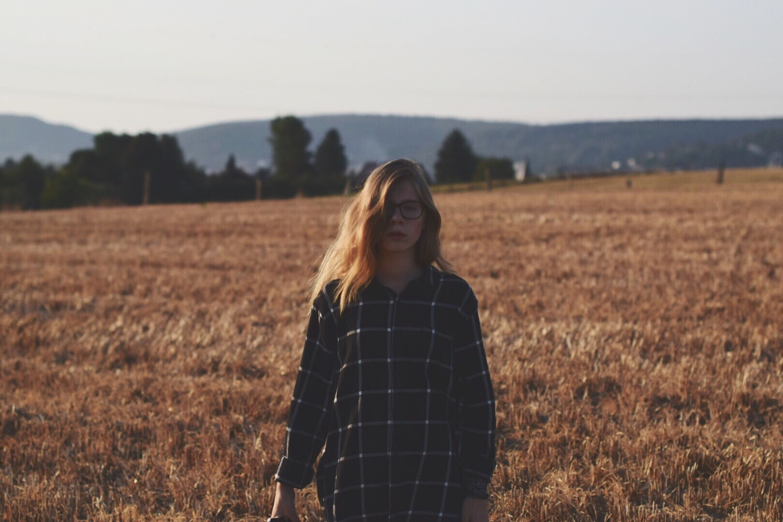 field, crop, landscape, rural scene, grass, agriculture, focus on foreground, front view, cultivated land, leisure activity, waist up, standing, casual clothing, grassy, farm, mountain, long hair, clear sky, nature, harvesting, tranquility, person, sky, scenics, growth, young adult, outdoors, beauty in nature, day