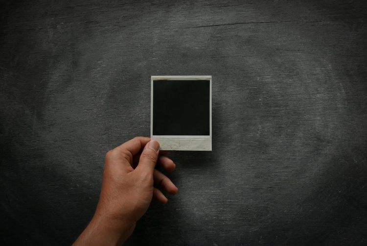 Cropped Image Of Man Hand Holding Instant Print Transfer Against Blackboard