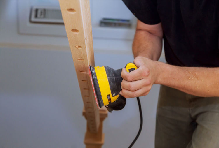 Midsection of carpenter using machinery on wood
