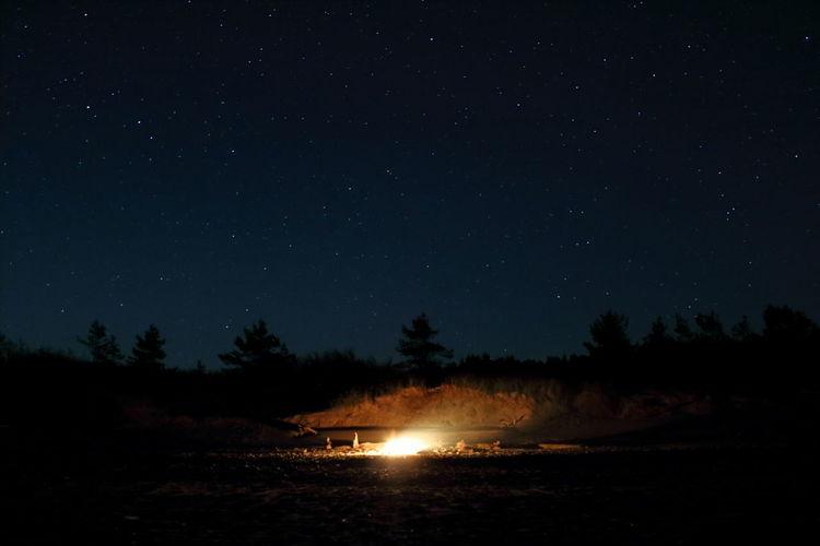 Bonfire on field against star field at night