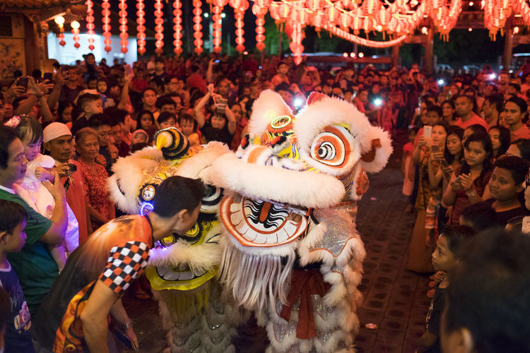 Benoa, Bali, Indonesia - January 28, 2017 : People praying and wishing a happy chinese new year on vihara satya dharma. Arms Raised Arts Culture And Entertainment Celebration Chinese Dragon Chinese New Year Costume Crowd Dancing Dragon Event Festival Group Of People Men Night Nightlife People Performance Real People Representation Traditional Dancing