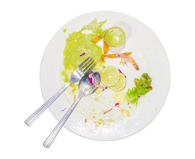 Food waste, after eating steak, fish sauce, chili, lime, purple cabbage, shrimp and dirty spoon in the dish. Isolated white background. Dish Eating Food Waste Isolated Spoon After Chili  Directly Above Dirty Eating Utensil Fish Food Food And Drink Fork Freshness Healthy Eating Kitchen Utensil Lime Plate Ready-to-eat Salad Sauce Studio Shot Table Knife Vegetable