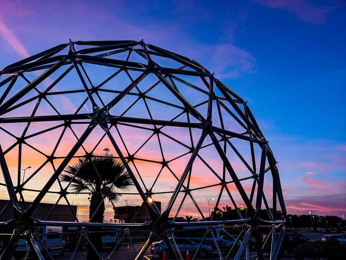 Low angle view of metallic structure against sky at sunset