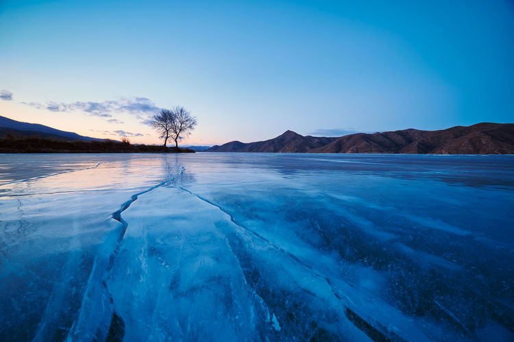 Scenic View Of Frozen Lake Against Blue Sky During Sunset