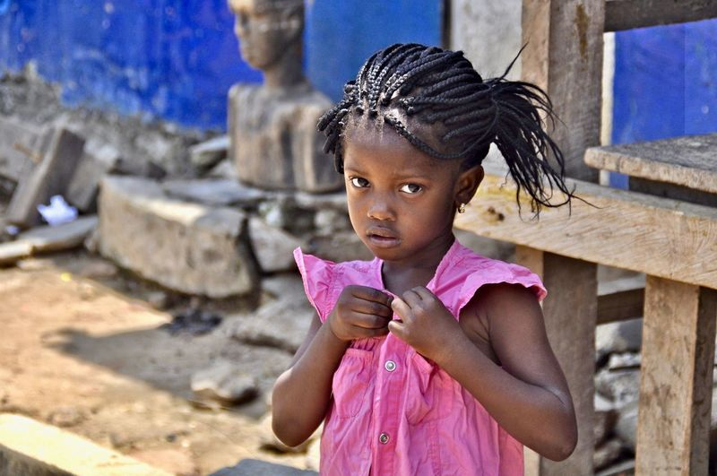 Child Childhood One Person Girls Cute Real People Innocence Front View Hairstyle African African Girl  Africa Pretty Girl African Beauty Focussed Closing Buttons Social Issue Faces Of Africa Poverty Developing Country Braided Hair Portrait Standing Timid Shyly