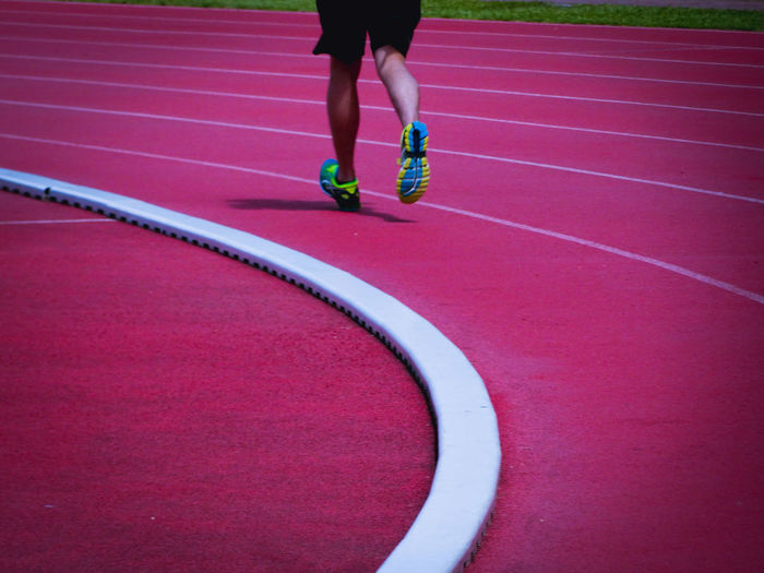 Low section of man running on running track