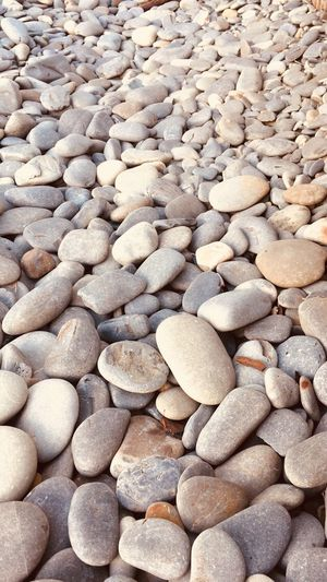 Pebbles on the beach Full Frame Backgrounds Stone Large Group Of Objects Pebble Solid Stone - Object Rock No People Abundance Beach Day Land Nature High Angle View Sunlight Textured  Pattern Outdoors Tranquility