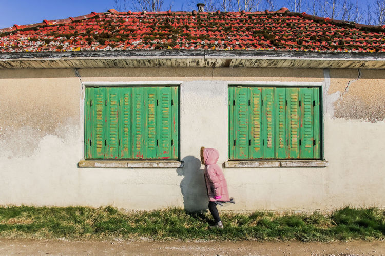 Girl Standing By House