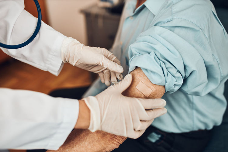 Doctor putting a plaster in place of injection of vaccine to senior man patient