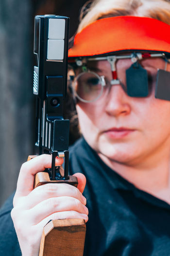 Close-Up Of Woman Practicing Target Shooting With Pistol