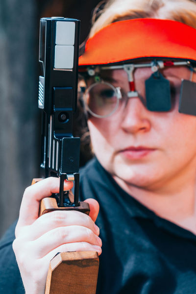 Sport Shooting Training. Woman Shooting Target Shooting Pistol Sport Shooting Gun Target Weapon Practicing Sports Training Training Female Woman Outdoor Barrel Competitive Sport Competition Protective Eyewear Handgun Concentration Technique Aiming Holding Serious Caucasian Ethnicity 30-39 Years One Person