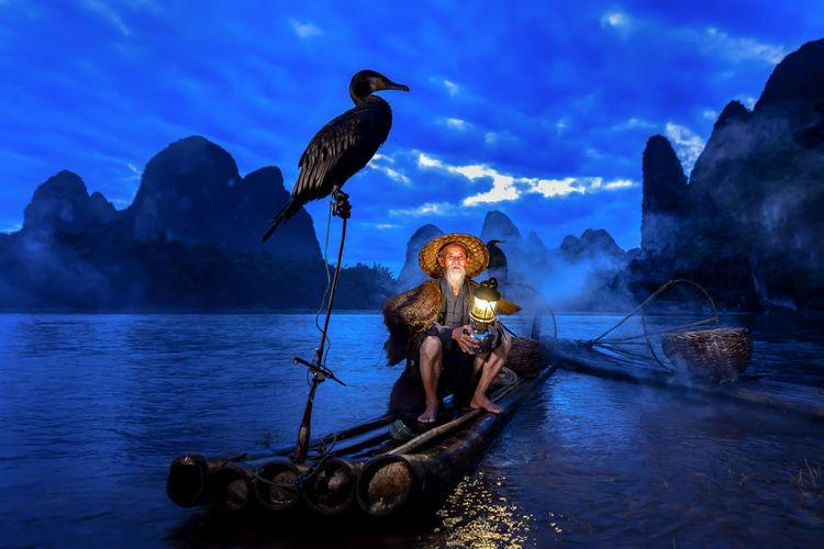 Birds Perching On Raft By Man Sitting Against Sky