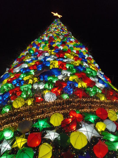 Low angle view of illuminated christmas tree against sky