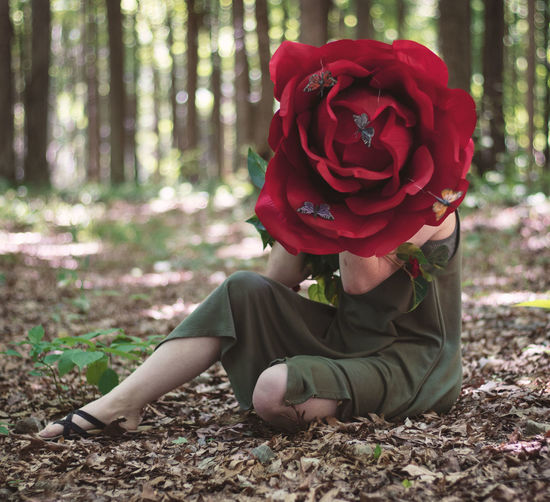Midsection of woman with red roses in forest