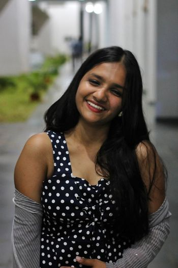Portrait of smiling young woman standing outdoors