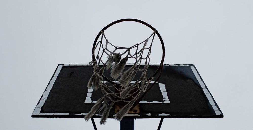 Low angle view of old basketball hoop against clear sky