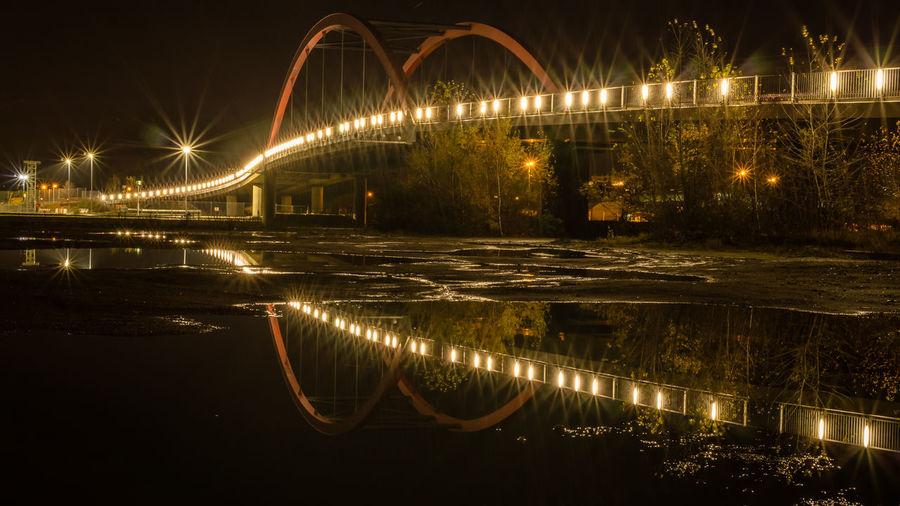 Illuminated Bridge Over Water At Night