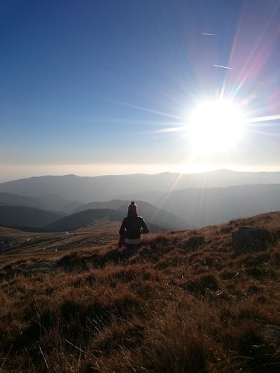 Rear View Of Woman Sitting On Mountain Against Bright Sky