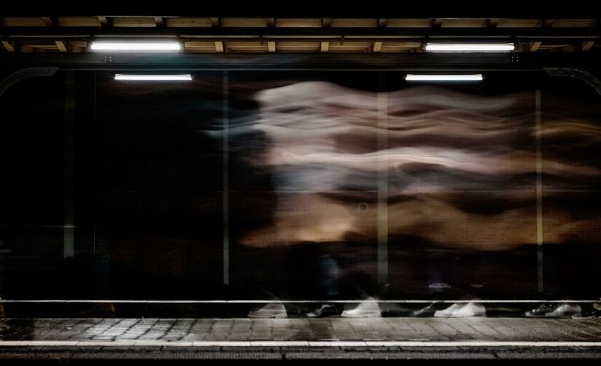 Blurred motion of woman seen through train window at railroad station