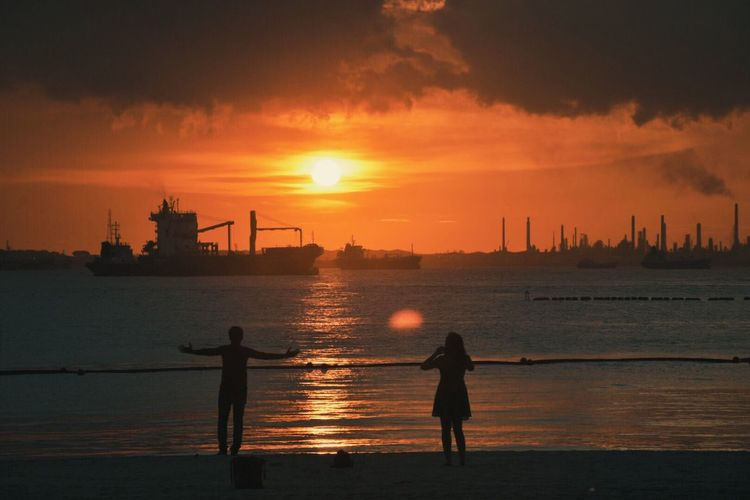 Rear view of silhouette people on sea during sunset