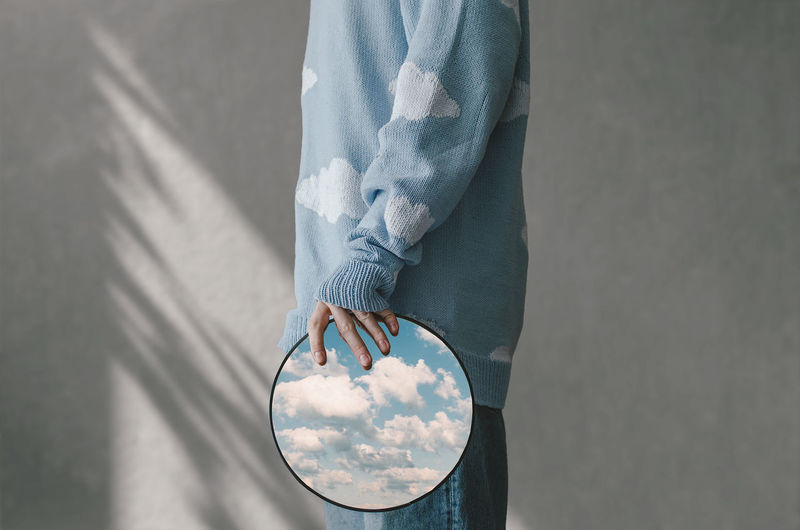 Low section in profile of man holding mirror in which the sky is reflected