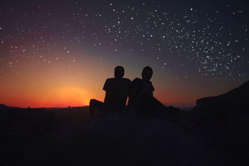 Silhouette men sitting against star field at sunset