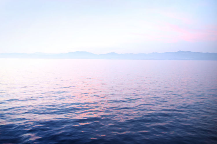 View of sunset over the calm ocean looking towards the horizon with pale pastel shades of blue, pink & purple. Beauty In Nature Scenics - Nature Tranquil Scene Tranquility Sky Water Sea Waterfront No People Nature Idyllic Mountain Copy Space Day Remote Rippled Cloud - Sky Non-urban Scene Horizon Outdoors Ocean Sunrise Dawn Tranquility Twilight
