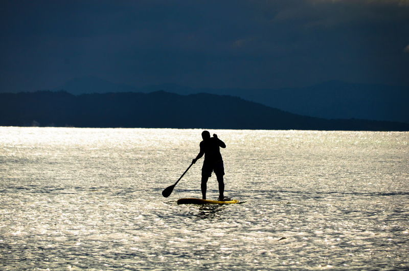 Silhouette man paddleboarding in lake