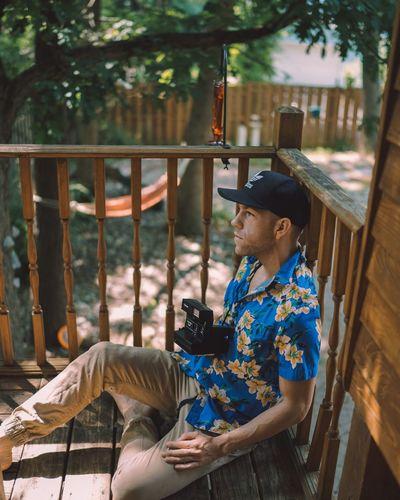 Man sitting on wood against trees
